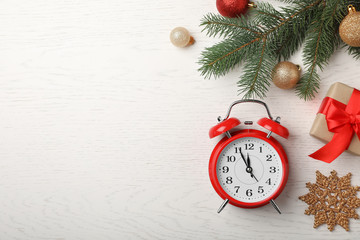Fotobehang - Flat lay composition with alarm clock and festive decor on wooden background. Christmas countdown