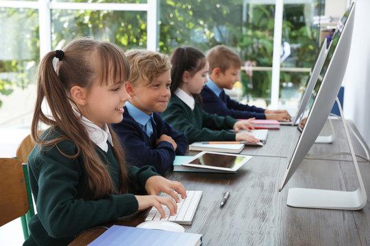 Little children in stylish school uniform at desks with computers