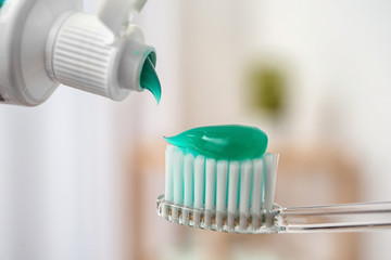 Applying paste on toothbrush against blurred background, closeup