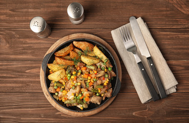 Pan with fried potatoes, meat and vegetables on wooden table, top view