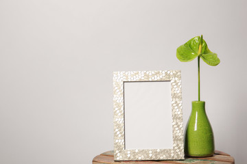 Blank frame and vase with flower on table against white background. Mock up for design