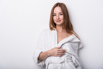 Beautiful red-haired girl in a white bathrobe on a light background