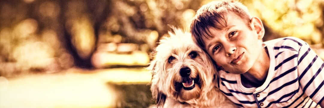 Portrait of boy with dog in park
