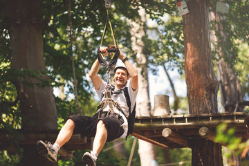 Middle aged man going by flying fox in forest rope park