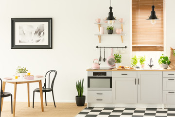 Industrial lamps and black dining chairs in a white kitchen interior with a modern oven and breakfast food