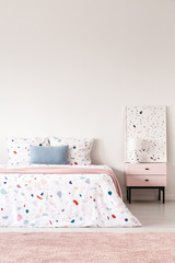 Blue pillow on patterned bed in white bedroom interior with pink carpet and poster. Real photo
