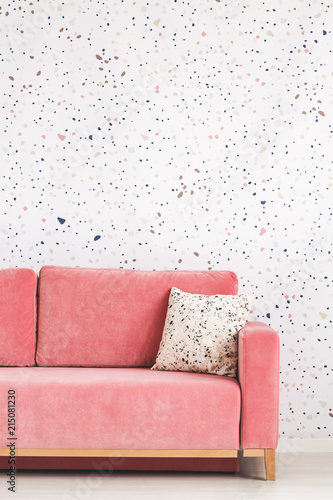 Pillow on pink sofa against patterned wallpaper in bright living ...