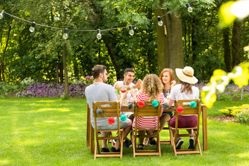 Group of smiling friends enjoying outdoor birthday party during summer
