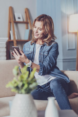 So pleased. Cheerful female person expressing positivity, looking at her smartphone