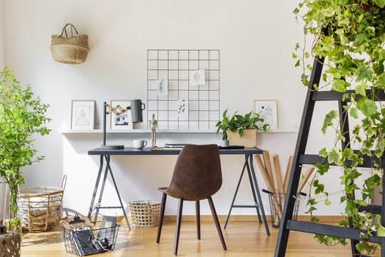 Brown chair at desk in white boho home office interior with plants and posters. Real photo