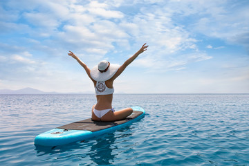 Frau in weißem Bikini und mit Sonnenhut genießt ihren Urlaub auf einem Surfbrett über blauem, sommerlichen Meer