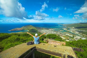Happy woman enjoying at top of koko head Crater trail.Aerial view of Hanauma Bay, Diamond Head and Honolulu, Oahu, Hawaii, USA. Hawaiian hiking in nature scenic landscape.Female hiker with raised arms
