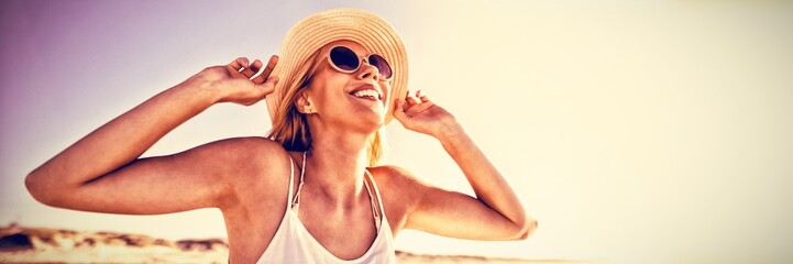 Happy woman wearing sunglasses and hat at beach