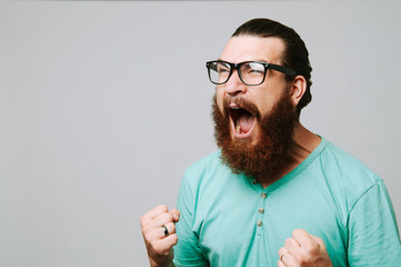 Screaming bearded man with eyeglasses over white background