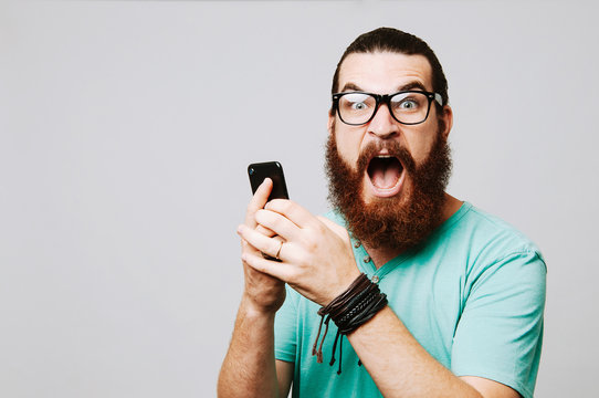 Amazed young bearded man looking at camera and holding phone