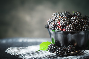 Ripe blackberry on a wooden table. Dark background.