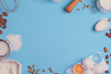 Baking ingredients for homemade pastry on blue background. Bake sweet cake dessert concept. Top view. Flat lay. Copy space. Toned