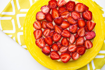 Beautiful and delicious strawberry cake stands on a yellow napkin.