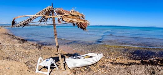 A white sailboat under an umbrella in a summer beach in Greece