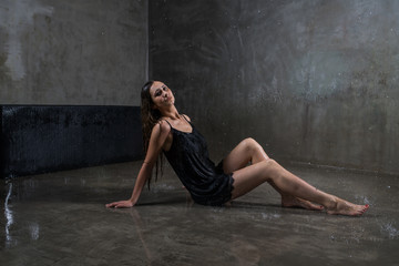 young beautiful sensual girl in a light dark dress, with dark hair sitting on the floor, in a room with gray walls, in which the rain falls. Aqua Studio