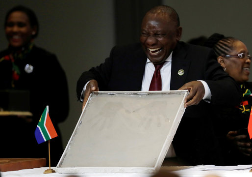 South African President Cyril Ramaphosa shows his hand prints during the BRICS Summit in Johannesburg