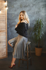 Beautiful and fashionable blonde model girl with big breast in silver skirt and in black satin blouse sits on a wooden stool, smiling and takes off her jacket at modern interior