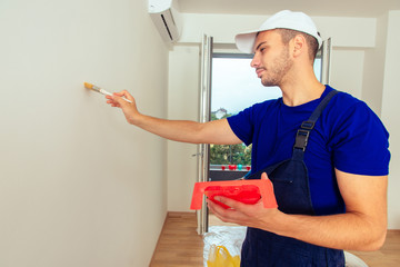 Young workman is painting  the wall with paintbrush. Home renovation concept.