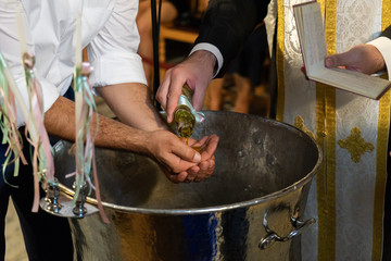 Orthodox christening. Priest puts baptism oil on the hands of godfather