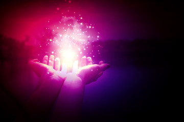 Magic particles on the palms of a woman on a dark, purple background. Magic particles, a flash of...