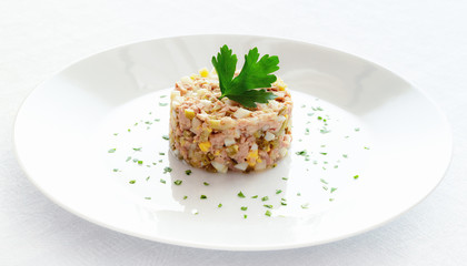 salad of cod liver, onion, egg,  and pickled cucumber decorated with chopped parsley and parsley leaf