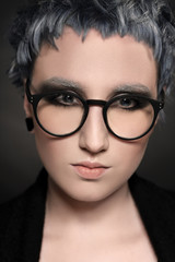 Portrait of girl with short dyed blue hair in eyeglasses on black background. Creative coloring and haircut.