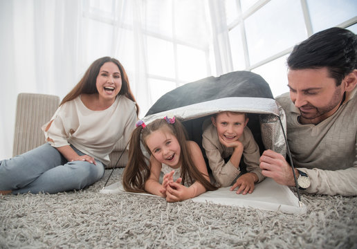 happy parents play with children in a tent in the living room