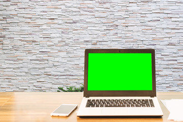 Mockup image of laptop with blank green screen,smartphone,coffee cup on wooden table of coffee wall large texture background.