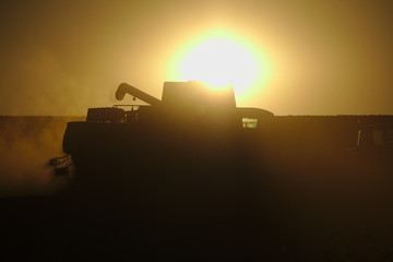 Harvester in a cloud of dust in front of the sun at sunset