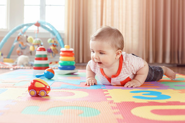 Portrait of cute adorable blond Caucasian smiling child boy with blue eyes crawling on floor in kids children room. Little baby playing with toys on playmat at home. Early education development