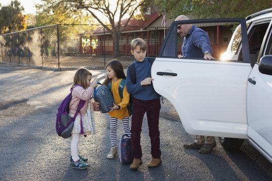 Siblings arrive at school through the car loop