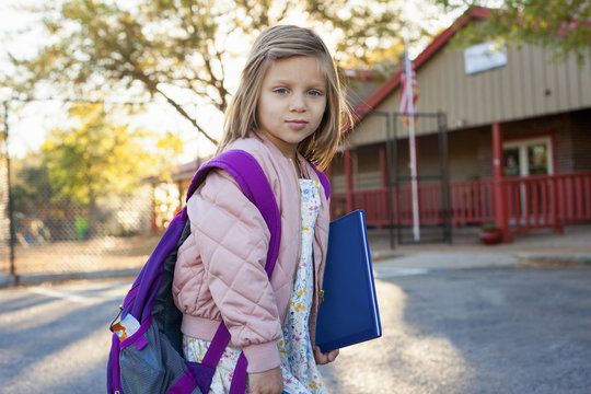 A girl standing outside building before school.