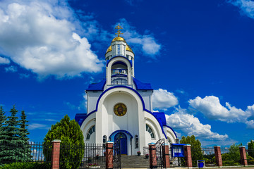 A small church on a background of blue sky and white clouds