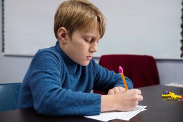 A boy in a classroom at school.