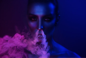 Nightlife. Beautiful Sexy Young Woman with glamorous mystical makeup vaping in Nightclub neon, exhaling smoke. Girl smoking