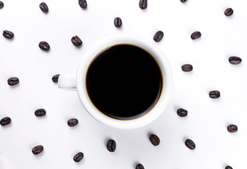 Black coffee in white cup with many coffee beans isolated on white background.