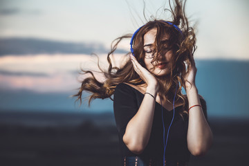portrait of a beautiful girl in headphones listening to music on nature