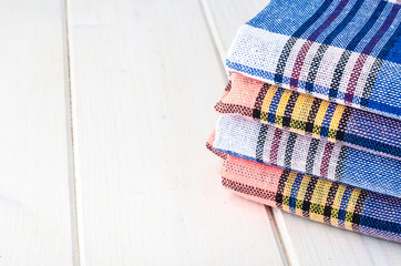 Stack of towels in cage on white wooden table