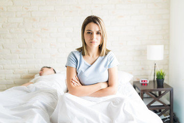 Unhappy Woman Sitting By Sleeping Man In Bedroom