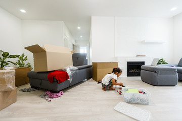 The happy little girl sits in a room boxes. Moving, purchase of new habitation or repair of a room.