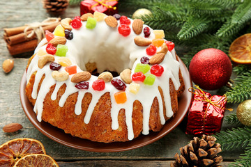 Bundt cake with fir-tree branches, bauble and gift boxes on wooden table