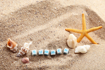 Inscription Summer by cubes with seashells on beach sand