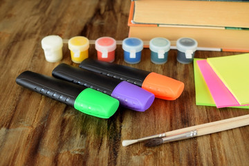 Paints, highlighters, brushes and stickers on a wooden table