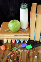 Books, stationery, green apple and milk on a wooden table