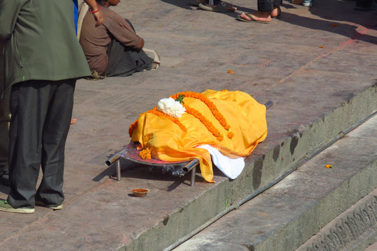 Dead body covered with white and orange textiles, waiting to be carried down the stairs to be dipped into the holy Bagmati River before cremation at the Pashupatinath Temple, Kathmandu, Nepal
